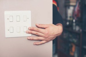 hand turning off light switch